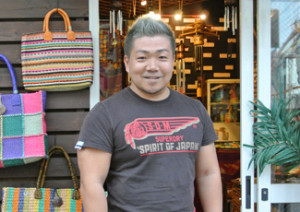 Mr. Hajime Yokota, the Representative Director of ACTION. He established a karate dojo within a Filipino orphanage, where he helps nurture the development of children through martial arts. He is shown here in front of a charity shop run by ACTION.